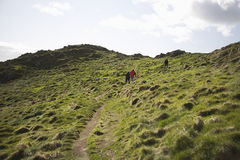 Three People Climbing Up Hill Royalty Free Stock Images