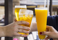 Three people clink glasses with drinks. At the restaurant Royalty Free Stock Image