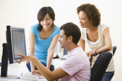 Three people on computer royalty free stock photo