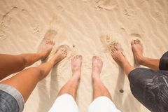 Three pair of feet in the sand. Three people different sex and age like a family with the feet in the sand. Summer time Stock Photo
