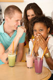 Three People Dining Out. Three people at a cafe drinking frozen beverages. Vertical shot Stock Photo