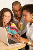Three People Dining Out Using a Laptop Royalty Free Stock Photography