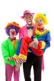 Three people dressed up as colorful funny clowns. Over white background Stock Images