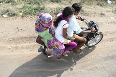 Three people drive bike without helmet Stock Images