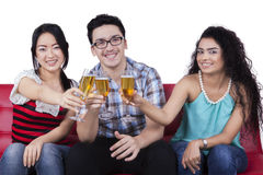 Three people enjoy champagne and toasts together Stock Photo