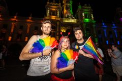 `Valencia, Spain`; 06 29 2019: People enjoy at Valencia`s Gay Pride Party at night. Three people and a gay flag at Valencia`s Gay Pride Party royalty free stock images