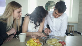 Three people have breakfast with fruit and rest for viewing the tablet. A man and two women sit at a table on which there is a plate with pieces of pineapple stock footage