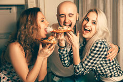 Three people having fun and eating pizza at a party Royalty Free Stock Photography