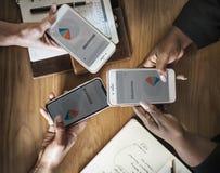 Three People Holding Phone Displaying Branding Pie Chart royalty free stock photo