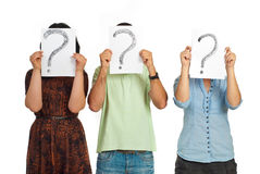 Three people holding question mark. Three casual people standing in a line and holding questions marks isolated on white background Royalty Free Stock Image