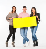 Three people holding a yellow paper Royalty Free Stock Photography