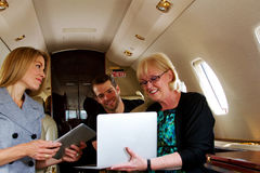 Three people on jet reviewing information Royalty Free Stock Photography