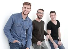 Three people leaning against the wall, smiling. Company of guys standing against a white wall stock photography