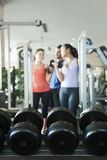 Three people lifting weights in the gym, focus on the weights Royalty Free Stock Photos