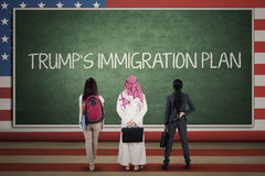 Three people look at Trump`s Immigration Plan word. Three people standing in front of chalkboard while looking at Trump`s Immigration Plan word with American royalty free stock photography