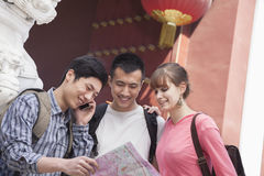 Three people looking at map. Stock Image