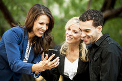 Three People looking at a Phone Royalty Free Stock Photos