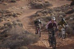 Three People Riding Mountain Bikes. Three people are riding mountain bikes uphill in a desert landscape. Horizontal shot Royalty Free Stock Images