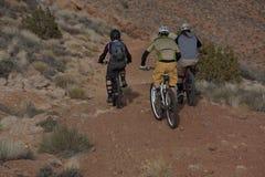 Three People Riding Mountain Bikes. In a desert landscape. Horizontal shot Stock Photos