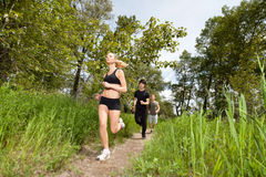 Three people running on pathway Stock Image