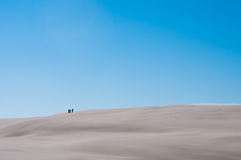 Three People On Sandy Dune With Blue Sky Background Royalty Free Stock Image
