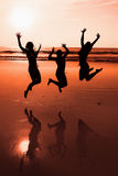 Three people silhouettes jumping on the beach Royalty Free Stock Photography