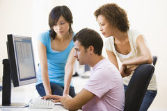 Three people sitting in computer room Royalty Free Stock Images