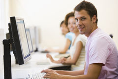 Three people sitting in computer room typing Stock Image