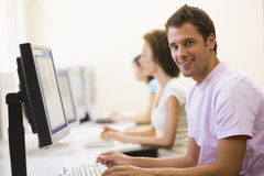 Three people sitting in computer room typing.  Stock Photo