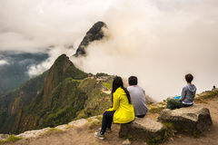 Three people sitting in contemplation of Machu Picchu from the terrace above on daytime. T Stock Images