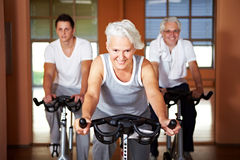 Three people in spinning class Stock Photos