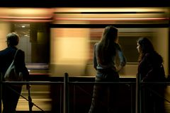 Three people standing at a bus stop in the night stock photo