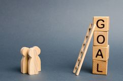 Three people are standing near the tower of cubes with the word goal. Evaluation of options and means to conquer the summit stock image