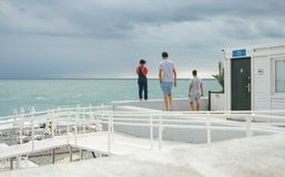 Three People Standing on White Surface Near Body of Water royalty free stock images