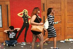 Three people on the street at South by Southwest. Three people on the street at Austin's South by Southwest passing a Barbarella wall mural. Thursday March 15 Royalty Free Stock Image