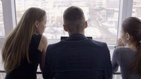 Three people are talking and looking out window in modern office. Young colleagues speaking while watching of cityscape from window indoors. Two women and man stock footage