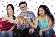 Three people toast with champagne glasses Royalty Free Stock Photography