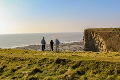 Three People On Top Of Hill Near Body of Water Stock Photography