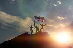 Three people on top of a mountain with the flag of the United States of America. Raising his hands up. Success and achievement, team. US Stock Photo