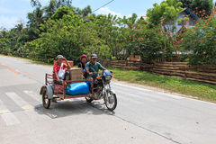 Three people on a tricycle in the Philippines. Puerto Princesa, Philippines - January 12,2015: Three people on a tricycle in the Philippines Stock Photography