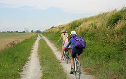 Three people with two bicycles along the cycle path in the natur Royalty Free Stock Images