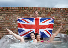 Three people with a union jack in a jacuzzi Stock Photography