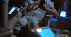 Three people using devices. Three people sitting in chairs and using their own devices. Evening stock video