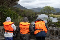 Three people waiting on a bridge wearing life jackets while they wait for a boat at the Meeting of the Waters, Ring of Kerry,. Ireland, on an overcast day royalty free stock photography