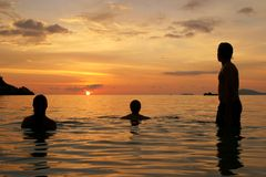 Three people waiting for the sunset. One man and two woman stand in the ocean and wait for the sunset. The picture has been taken in Thailand on the Isle Koh Stock Photo