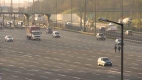 Three people walking between traffic on motorway stock footage