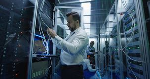 Three people working in a data center with cable. Medium shot of three people working in a data center with cable to repair rows of server racks stock photo