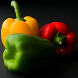 Three peppers. Red, yellow and green pepper on black background Royalty Free Stock Photos