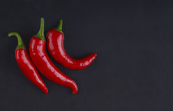 Three peppers on a black background. Stock Photos