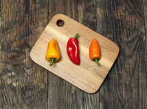 Three peppers on a board. Royalty Free Stock Images